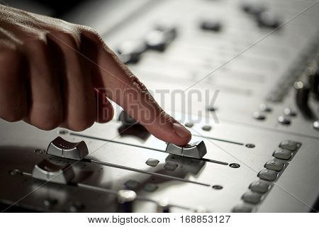 music, technology, people and equipment concept - hand using mixing console in sound recording studio