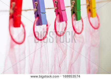 Unrolled latex condoms on white background, studio shot