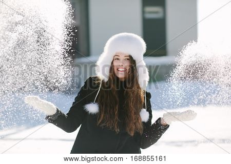 Girl playing with snow in park.