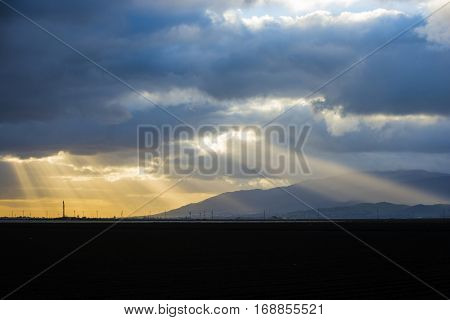 Gorgeous morning sunrise sunshine through clouds on lush rich farm land soil and hillsides