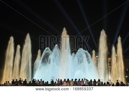 BARCELONA, SPAIN - JULY 29, 2016: Barcelona (Catalunya Spain): the Magic Fountain (Fuente Magica Font Magica) of Montjuic with plays of colorful lights at evening and people in silhouette watching at the show