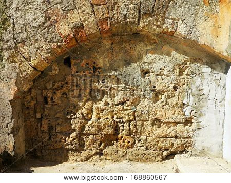 Entry and exit to the catacombs laid wall of natural stone