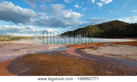 Grand Prismatic Hot Spring under western cloudscape in the Midway Geyser Basin in Yellowstone National Park in Wyoming USAGrand Prismatic Hot Spring under sunset clouds in the Midway Geyser Basin in Yellowstone National Park in Wyoming U S A