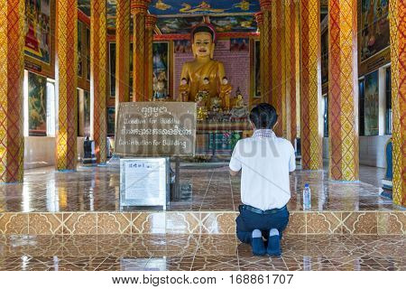 Rolous, Cambodia - January 04, 2017: View of a cambodian young man in prayer in front of Buddha statue in the modern Theravada Buddhist monastery adjacent to the historical Lolei temple