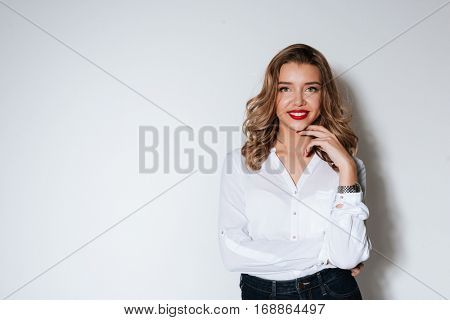 Portrait of a happy smiling woman standing and posing with hand on chin over white background