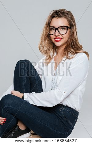 Portrait of a smiling pretty woman in eyeglasses looking at camera on white background