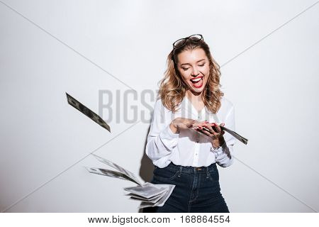 Happy excited woman throwing money over white background