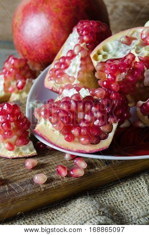 Juicy pomegranate a delicious fruit on wooden background.