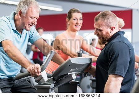 Group with senior man and woman spinning on fitness bikes with personal trainer at gym