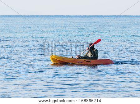 Fisherman In Green Jumpsuit Floats In Orange Kayak On Sea