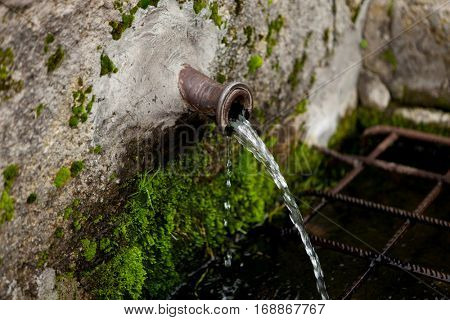 Pipe clean water pouring from a natural source