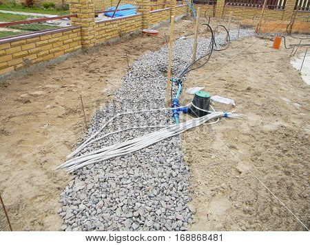 Building new concrete pavement for garden pathway. Foundation for paving with electrical wires and watering equipment garden irrigation supplies.