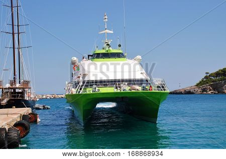 ALONISSOS, GREECE - JUNE 21, 2013: Hellenic Seaways catamaran ferry Flying Cat 5 arrives at Patitiri harbour on the Greek island of Alonissos. The 39mtr vessel was built in 1996 in Norway.