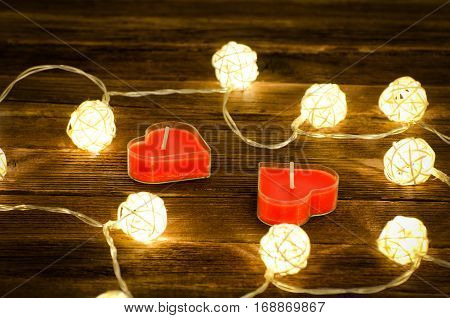 Two red candles in the shape of a heart and glowing lanterns made of rattan on a wooden background. Close-up