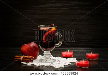 Mulled wine with spices on a lace napkin. Candles in the shape of a heart cinnamon sticks and apple. Black wood background