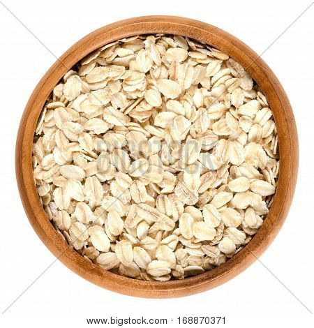 Oatmeal, rolled oats in wooden bowl. Dehusked, hulled oats, rolled into large whole flakes. Porridge oats, used in granola or muesli. Isolated macro food photo close up from above on white background.