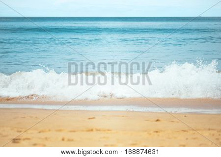 Close up photography of colorful sea wave with sunny blue sky on horizon from white sand beach in Phuket, Thailand. Outdoor landscape of big ocean waves in Southeast Asia.
