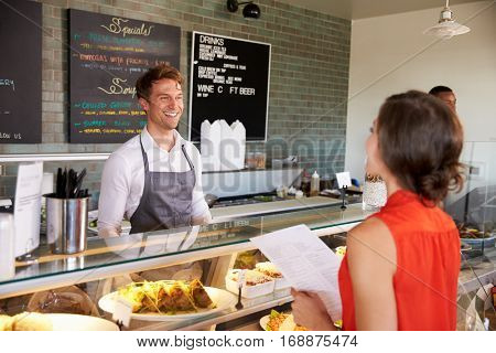 Man Working Behind Counter In Delicatessen Taking Food Order
