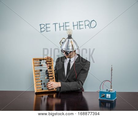 Be the hero text on blackboard with businessman and abacus