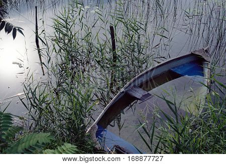 Boat half cast : small wooden boat full of water in a lake