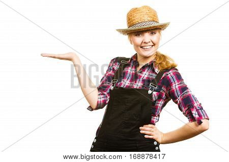 Gardening concept. Attractive woman in dungarees pink check shirt and sun hat showing something on her hand. Isolated background