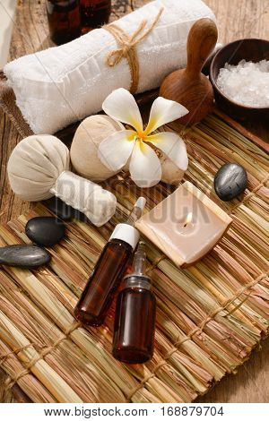 Tropical bath spa treatment on mat with wooden background