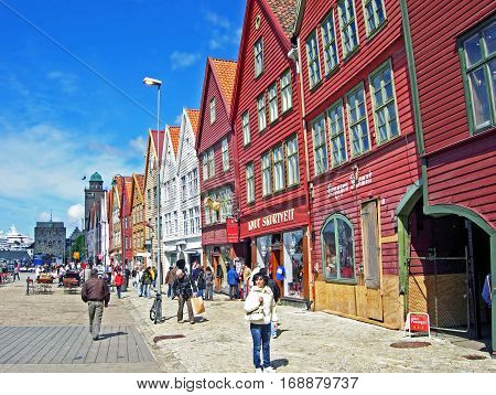 Bergen, Norway - June 8, 2009: People walk along the historic houses of the old town location Bryggen in Bergen (Norway).
