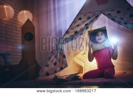 Child in an astronaut costume with toy rocket playing and dreaming of becoming a spacemen. Happy kid plays in tent. Funny lovely girl having fun in children room.