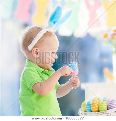 Kids celebrate Easter. Funny happy baby in bunny ears playing with Easter eggs. Child having fun on Easter egg hunt. Family home decoration pastel bunny banner colorful Easter eggs and flowers