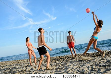 four young people man and woman playing beach volley together by the sea in sunny summer vacation day