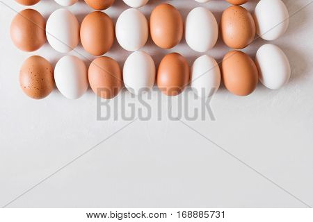 White and brown eggs in the shape of a rectangle on a white background. Easter Concept Photo