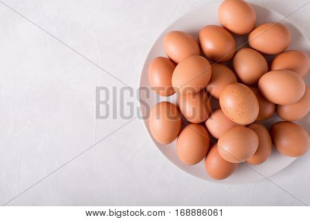 Brown eggs on a white plate on a white background. Eggs. Easter photo concept. Copyspace