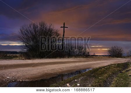 Country road at dusk and wooden cross