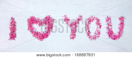 Lettering I Love You. Beautiful Decorative floral arrangement with a Declaration of love of pink flowers lilac on light wooden background. Wide Horizontal Web banner