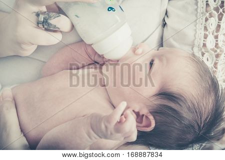 Closeup Photo Of Feeding Sweet Baby With Milk From Bottle