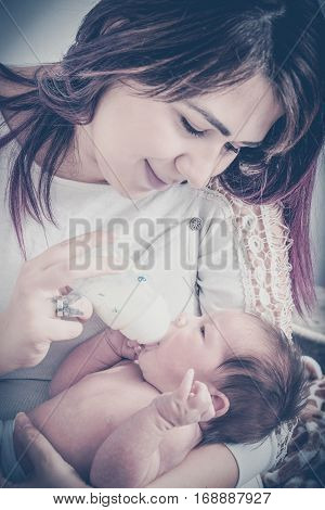 Smiling Mother Feeding Milk To Baby From Bottle At Home