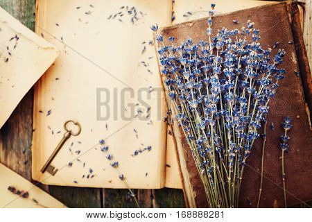 Retro still life with vintage books key and lavender flowers nostalgic composition on wooden table top view.