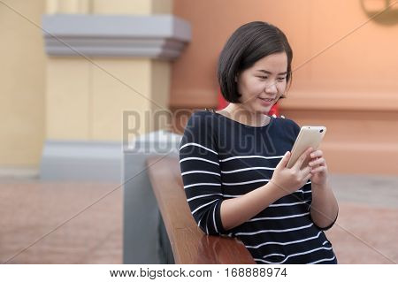 Weekend lifestyle scene of adult Asian woman using mobile phone. Urban lifestyle on weekend with technology.