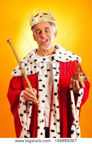senior man in king's dress, making faces