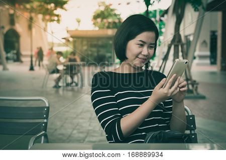Weekend activity scene of adult Asian woman looking on mobile phone at coffee shop with vintage filter effect. Urban lifestyle with technology concept.