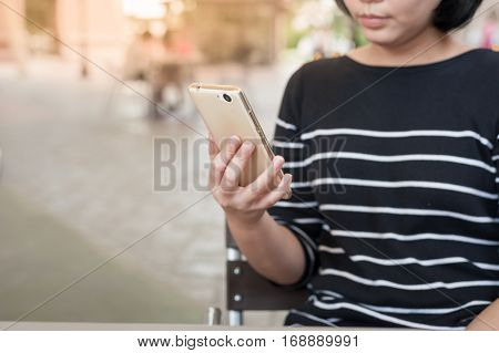 Weekend activity scene of adult Asian woman watiching on mobile phone at coffee shop. Urban lifestyle with technology concept.