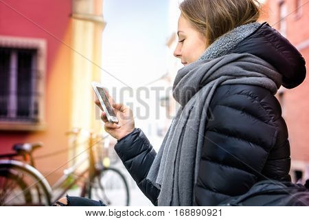 Teenager girl typing text message on phone in city street at winter - Young female student addicted by social network head down to mobile - Lifestyle concept with bike background sunbeam and shadows