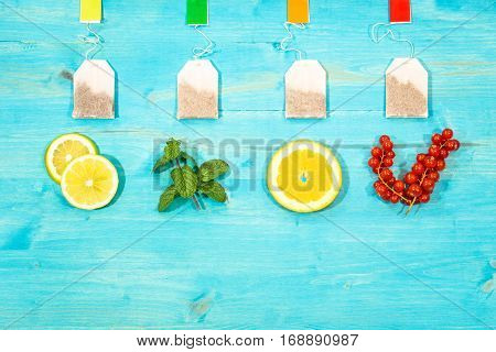 Flavored teabags fresh fruit top view on aquamarine wood table with copy space - Mint leaf lemon orange and cranberries colorful still life composition light blue background image from above
