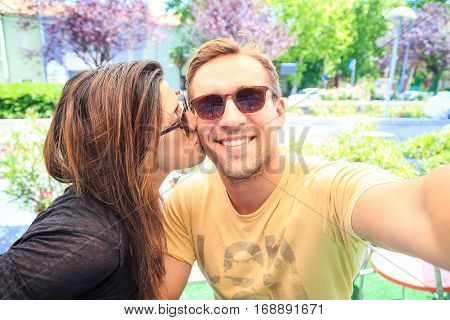 Couple in love are sitting in bar and take a selfie memory picture. Lovers are chilling and drinking a coffee in a sunny day after shopping day in the city. Image of smiling young joyful best friends