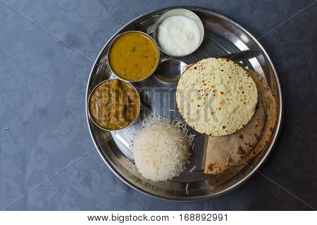 North Indian thali a tipical meal served on stainless steel plate on blue table. Directly above.