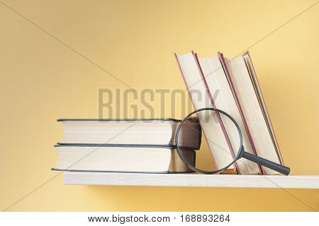 Stack of books on wooden shelf on green wall background. Education background. Back to school. Copy space for text.