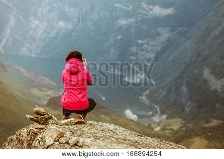 Tourism vacation and travel. Female tourist enjoying Geirangerfjord and mountains landscape from Dalsnibba viewpoint Norway Scandinavia.