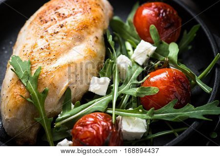 Healhty food lunch menu. Grilled chiken fillet and fresh salad from rukkola feta cheese and cherry tomatoes