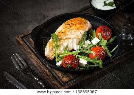 Healthy food lunch menu. Grilled chicken fillet and fresh salad from arugula feta cheese and cherry tomatoes.