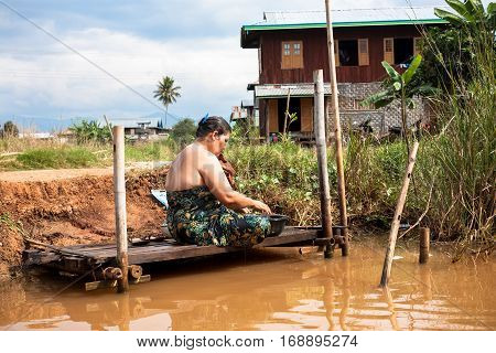 Inle Lake Myanmar - 2017 January 2 : A woman bathing and washing herself in a canal on the Inle Lake in central Myanmar